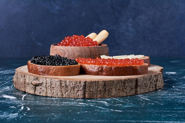 Red and black caviar toastes on wooden board.