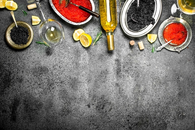 Red and black caviar with wine and lemons. on rustic background .