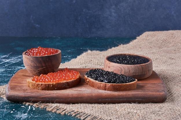 Caviale rosso e nero su tavola di legno.