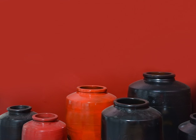 Red and black ceramic jar on red background