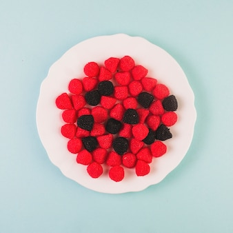 Red and black cranberry candies on plate