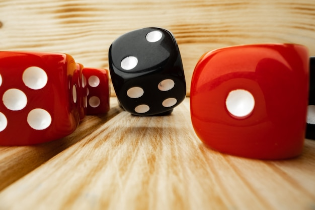 Red and black dice cubes on wooden background