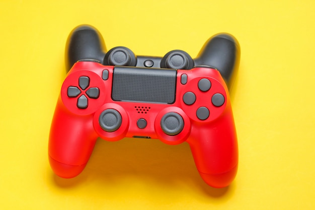 Red and black gamepad on yellow background close up