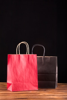 Red and black paper bag on wooden surface against black backdrop