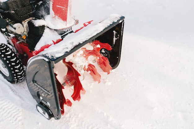 Red-black snowblower machine in the process of work