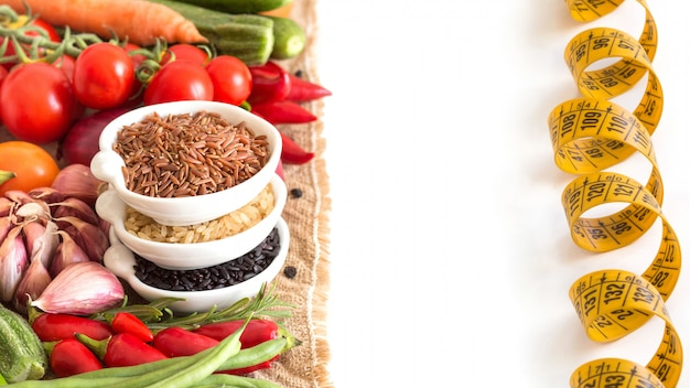 Red, black and unpolished organic rice and raw vegetables isolated on white close up