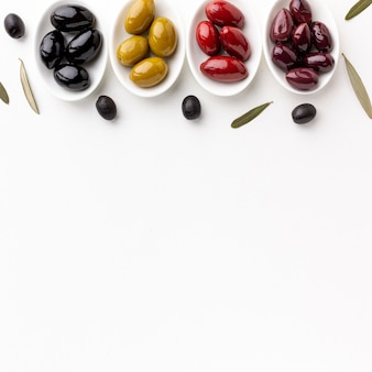 Red black yellow purple olives on plates with copy space