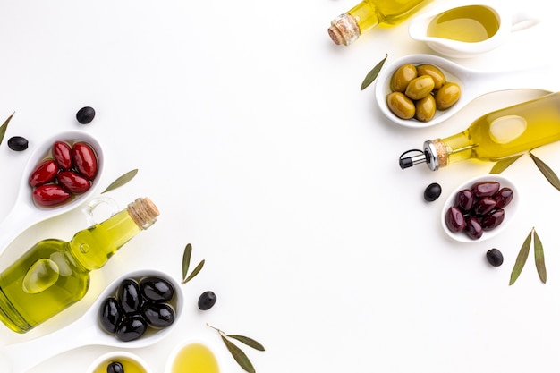 Red black yellow purple olives in spoons with oil bottle