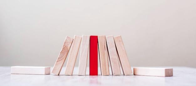 Красный блок и деревянные блоки стоят на столе. работа в команде, единение, управление рисками, решение, лидер, стратегия, разные и уникальные концепции