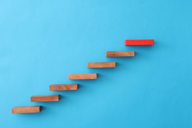 Красный блок, стоящий над деревянными на синем фоне, крупным планом, концепция курса личного роста