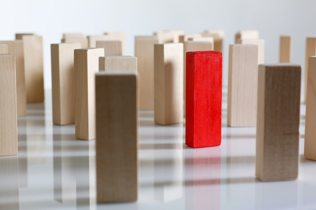 Red block surrounded by wooden blocks standing