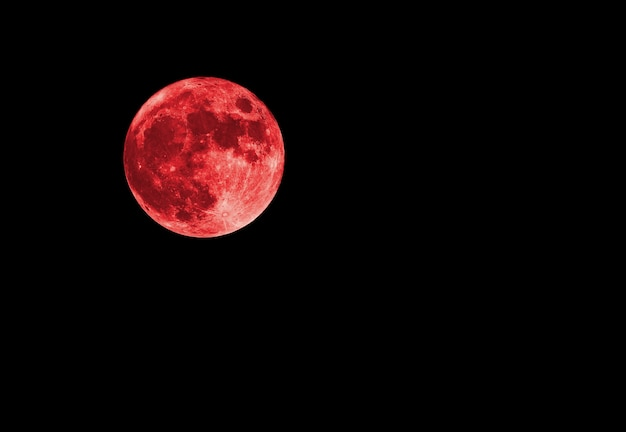 Red bloody moon on black sky as background, full moon
