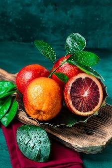붉은 피 묻은 오렌지 반으로 잘라 어두운 녹색 배경, copyspace와 세로 사진에 가까이