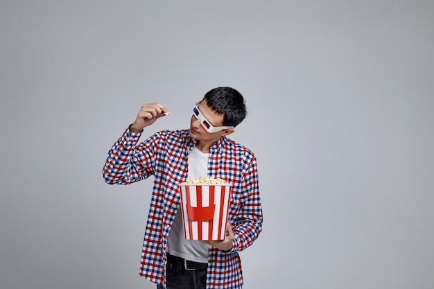 In red-blue 3d glasses looking at popcorn in bucket isolated on gray