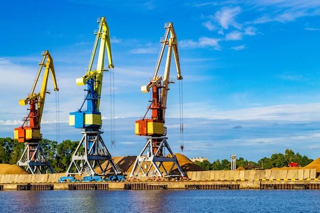 Красные, синие и желтые грузовые краны стоят на берегу реки венты. вентспилс, латвия, прибалтика