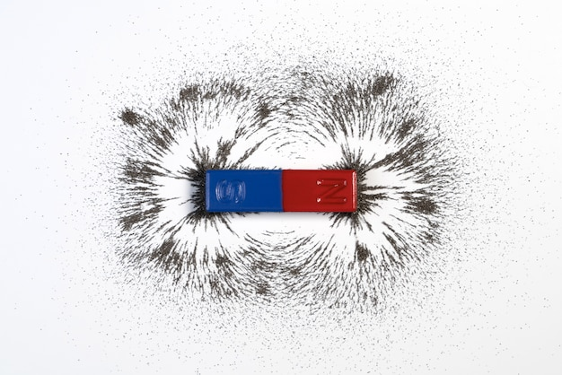 Red and blue bar magnet with iron powder magnetic field on white background.