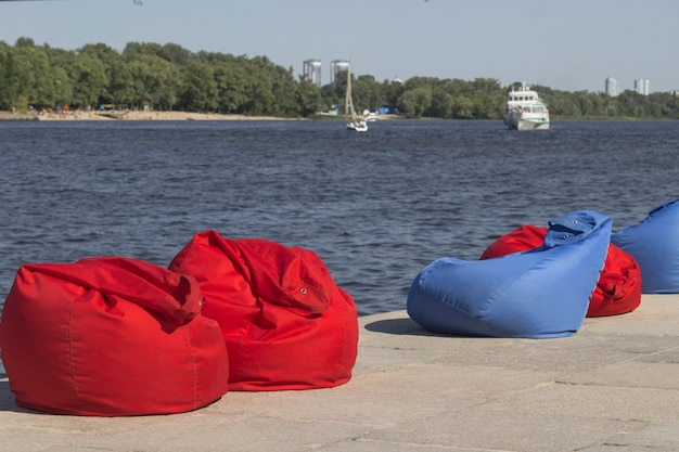 Red and blue beach bean bags on the river bank