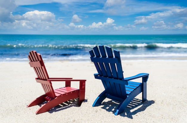 Red and blue beach chairs near ocean