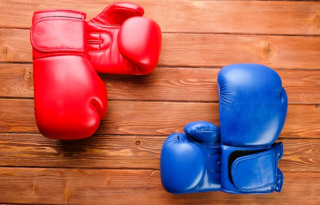 Red and blue boxing gloves on a wooden background