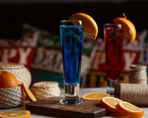 Red and blue cocktails with orange slices on the top