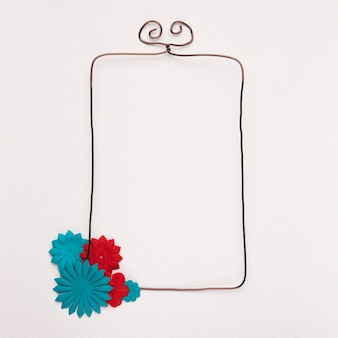 Red and blue flower on the corner of wired rectangular frame against white backdrop