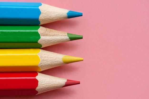 Красные, синие, зеленые и желтые карандаши на розовом фоне крупным планом