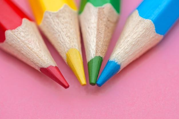 Красные, синие, зеленые и желтые карандаши на розовой поверхности крупным планом