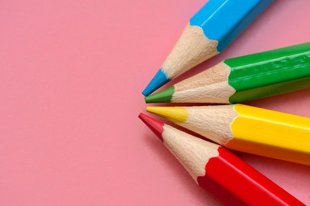 Red blue green and yellow pencils on a pink background