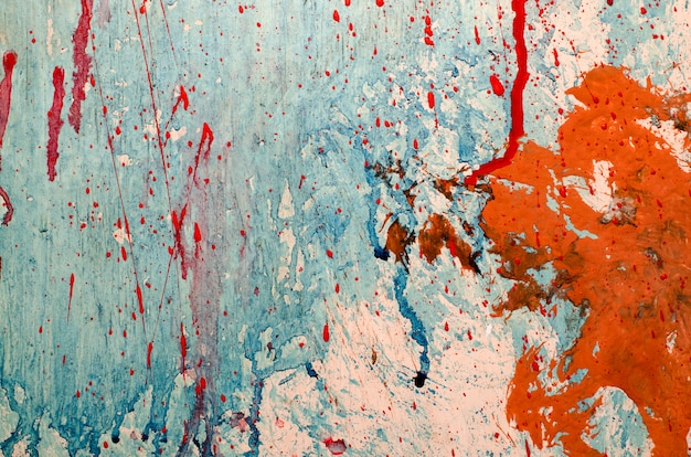Red and blue paint splashes on grunge wall