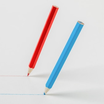 Red and blue pencils drawing parallel lines. the concept of cooperation.