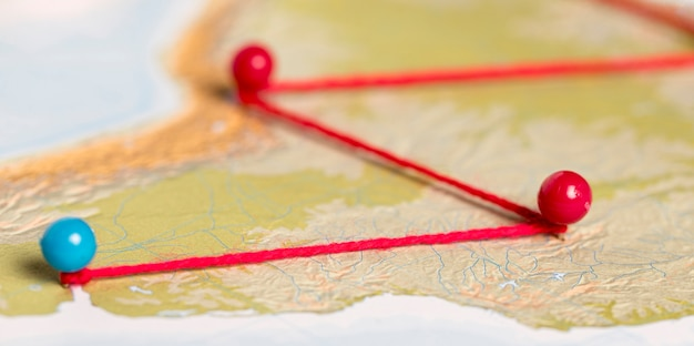 Red and blue pushpins with thread on route map
