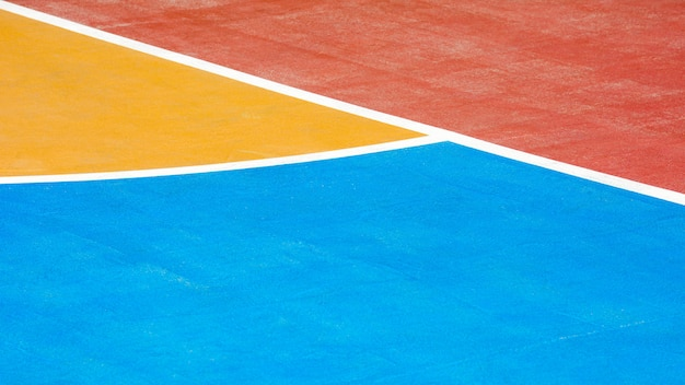 Red, blue and yellow concrete basketball court - close up