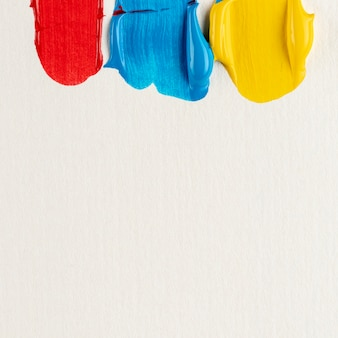 Red, blue and yellow paint with copy space