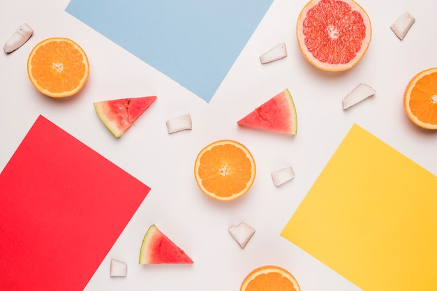 Red blue yellow sticky note and sliced watermelon orange grapefruit coconut