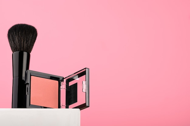 Красные румяна черной кистью на белой подставке, витрина для косметики. женский бьюти-аксессуар для профессионального макияжа. средство для идеального тона кожи. скопируйте пространство.