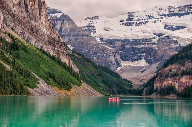 Красная лодка в озере возле горы