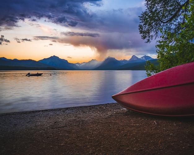 夕焼け空の下で美しい山々に囲まれた海の近くの赤いボート