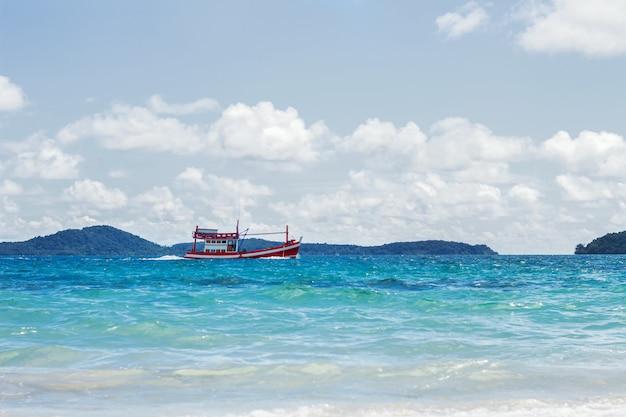 Красная лодка плывет по океану на фоне облачного неба.