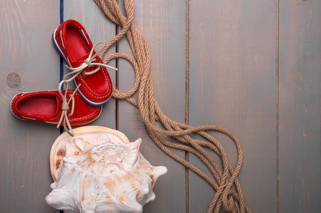Red boat shoes near big shell and rope on wooden.