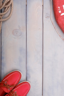 Red boat shoes on wooden background near lifebuoy and rope.