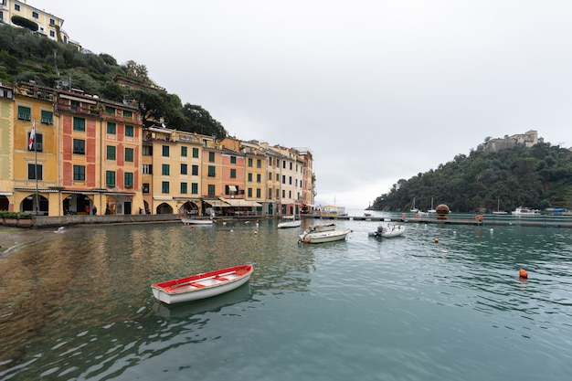 Red boat on water with colorful houses at square of portofino.