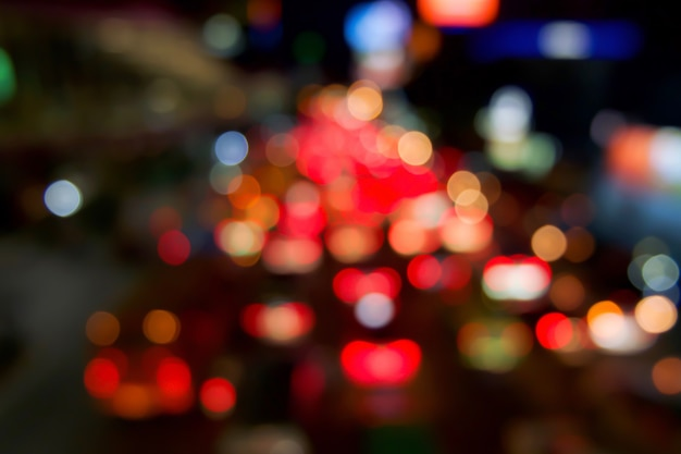 Red bokeh light from car on road in the city at night time. defocused of night traffic.