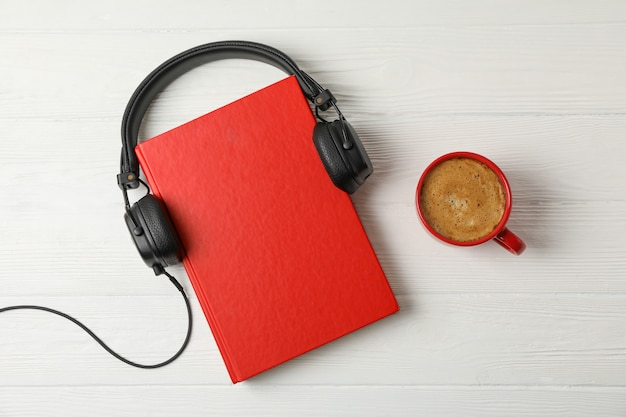 Red book, headphones and coffee cup on wooden space, space for text
