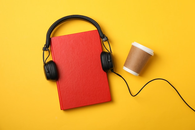 Red book, headphones and coffee cup on yellow space, space for text