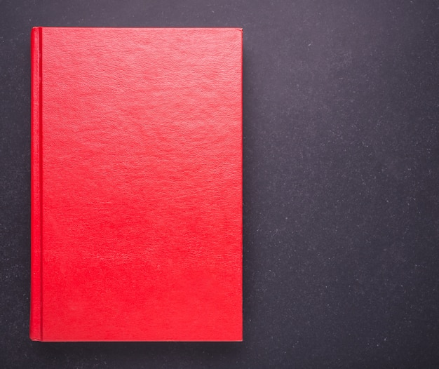 Red book with blank empty cover on black stone table background. top view