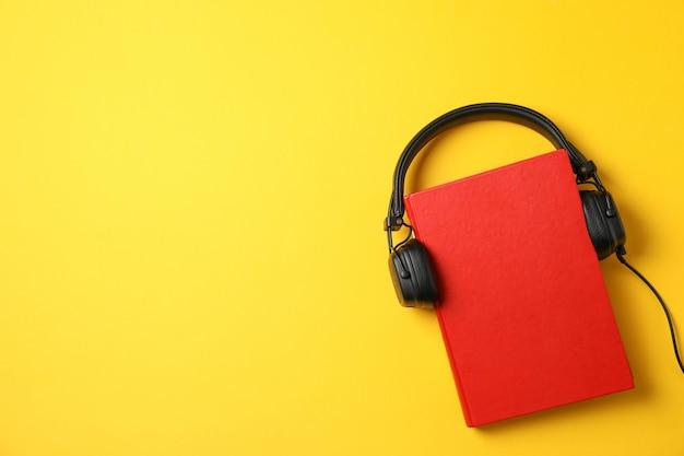 Красная книга с наушниками на желтом фоне, вид сверху