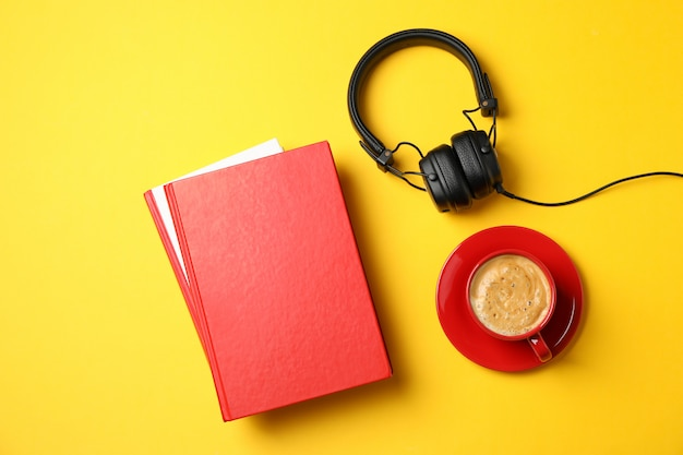 Red books, headphones and cup of coffee on yellow background, top view