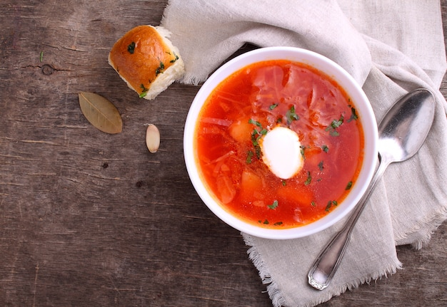 Red borscht soup in white bowl with sour cream and parsley