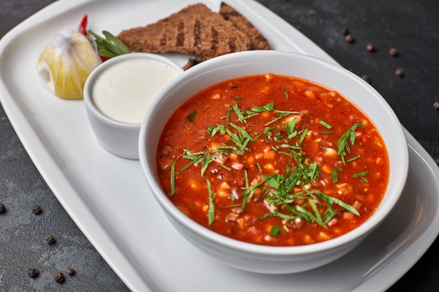 Red borscht on a white plate with bread and sour cream, on a dark background