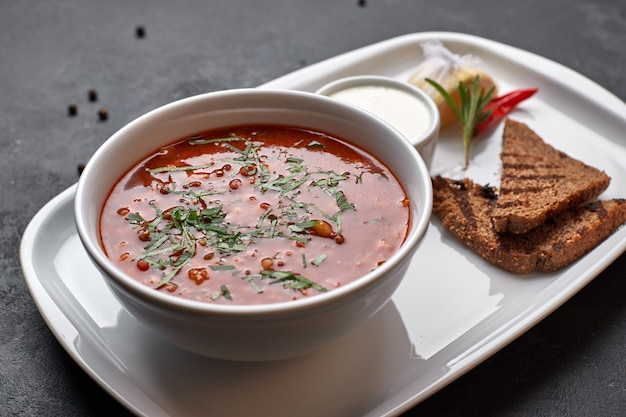 Red borscht on a white plate with bread and sour cream